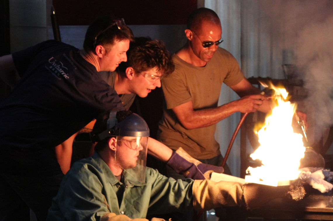 an artist collaborating with glass blowers using a large open fire