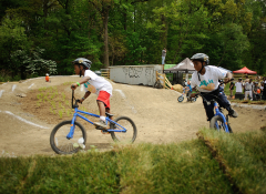 Two black kids on bicycles having fun on a dirt trail