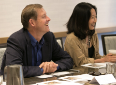 A white man and east asian woman sit side-by-side at a table