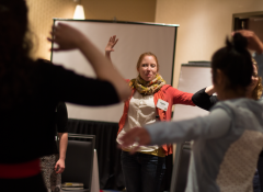 A young white woman leads a group in a choreographed dance exercise.