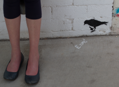 A white woman's legs next two a graffiti image of a bird