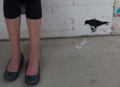 A white woman's legs next two a graffiti image of a bird