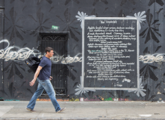 Image of a white man walking down the street in front of a piece of street art