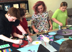 Four white teens working on an art project