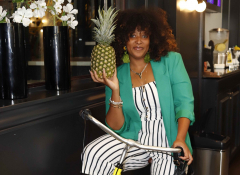 A young Black woman in a green blazer on a bicycle holding a pineapple.