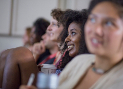 A young black woman looking ahead, two women flank her out of focus.