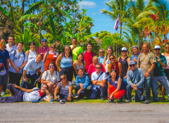 Two dozen people posing for a group photo in Hawai'i