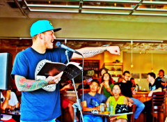 Carlos Contreras by microphone reading spoken word poetry.