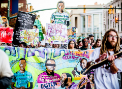 Image of a group of protestors with bright signs featuring black youth