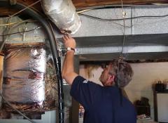 A man fixing a fiber cord above his head.