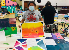 A Lakota teen standing by a table displaying their art.