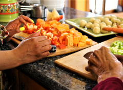 Two pairs of hands cutting vegetables.