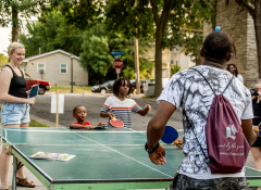 A young white woman and a young black man play ping pong