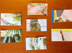 A series of postcards on a brown wooden table