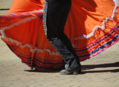 Photo of the legs of a man and woman dancing ballet folklorico in traditional wear