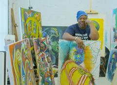 A black artist standing behind his paintings