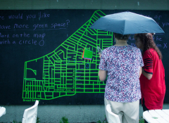 Two people with an umbrella viewing a schematic