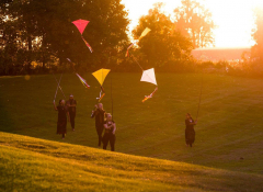Image of a group of people flying kites.