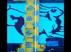 A bright blue mural of a rabbit on a brick wall