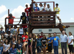 A large group of teens and adults posing around a wooden structure