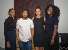 A group photo featuring three black women and one black man.