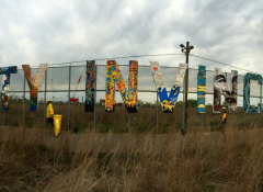 Art installation featuring letters on a chain-link fence