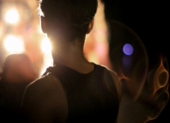 Photo of a young dancer taken of the back of their head as they are illuminated by the light.