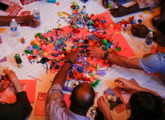 Many hands reaching for several lego pieces on a table