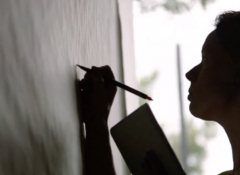 Silhouette of a woman writing on a board