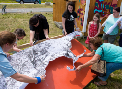Community members collaborate on the installation of a wheat paste mural depicting a child and elder gardening together.