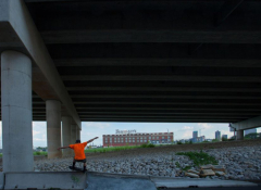 Young black child playing under an interstate