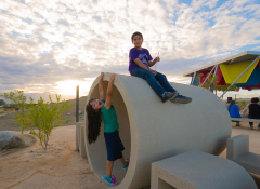 Two kids playing by a large cement cylinder in a park