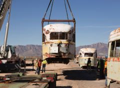 An old and rusted transnational trolley being held in the air by a crane