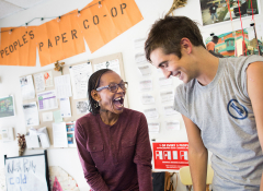 A black woman and a white man smiling and working at the People's Paper co-op