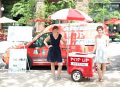 "Two white women standing with a popsicle stand that reads ""pop up meeting"""