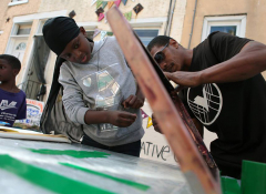 Two young black men working on an art project