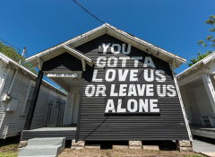 "A house painted black with the words ""You gotta love us or leave us alone"" on it"
