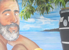 Mural of a Puerto Rican man with the blue skies and ocean behind him
