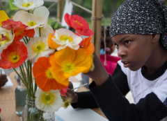 A young black girl working on paper flowers