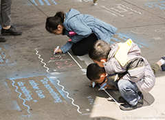 Three young kids drawing on the sidewalk with chalk