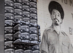 A giant black and white mural featuring a trolley pattern next to a man dressed as a conductor
