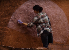 A Native woman painting a semi-circle on a mountain wall