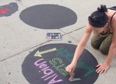 A young woman doing a chalk drawing on the side walk