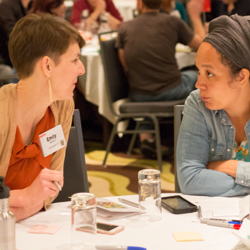 Two women sitting at a table speaking to each other.