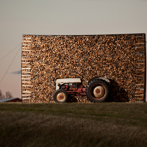 An art installation featuring a tractor and bundles of wood
