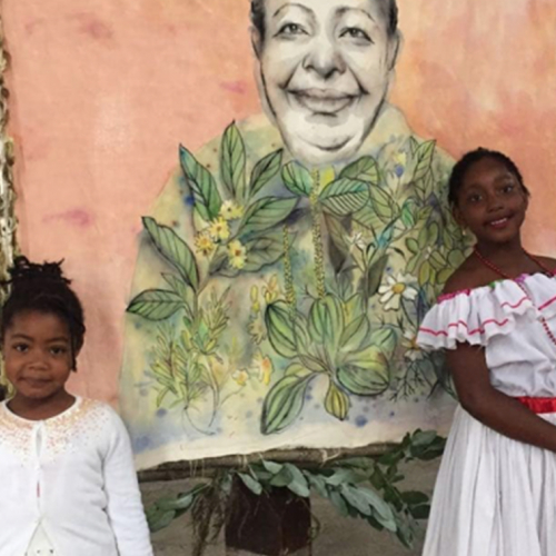 Two young black girls standing in front of a painting