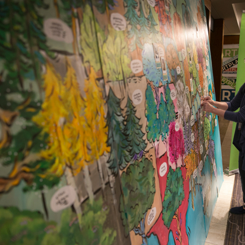 A woman adhering her photo on a mural of the United States commissioned for the ArtPlace Summit