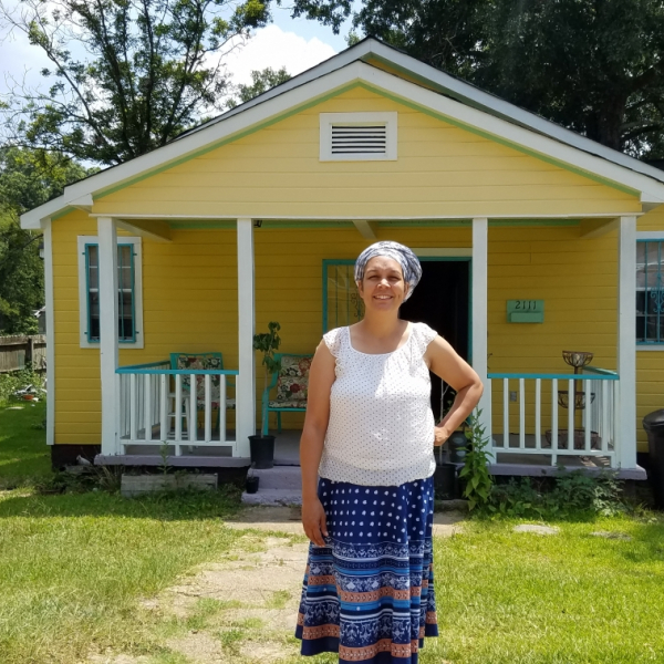 Nia Umoja of the Cooperative Community of New West Jackson standing in front of a yellow  house