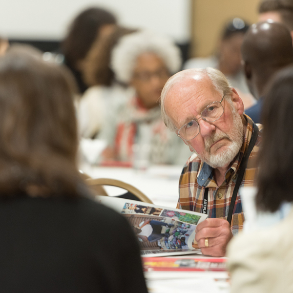 An older white man sitting at a table listening to those around him.