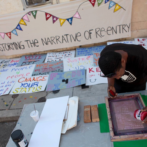 """Image of an African American artist silk screening a poster with the text """"Transforming the Narrative of Re-Entry"""" painted on a banner behind him."""